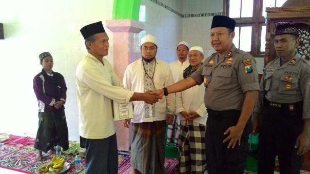 Kapolres Situbondo didampingi penasehat DMI saat menyerahkan tali asih kepada pengurus takmir Masjid